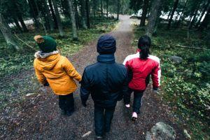 Kuvassa kolme henkilöä kävelee metsätiellä selin kameraan.