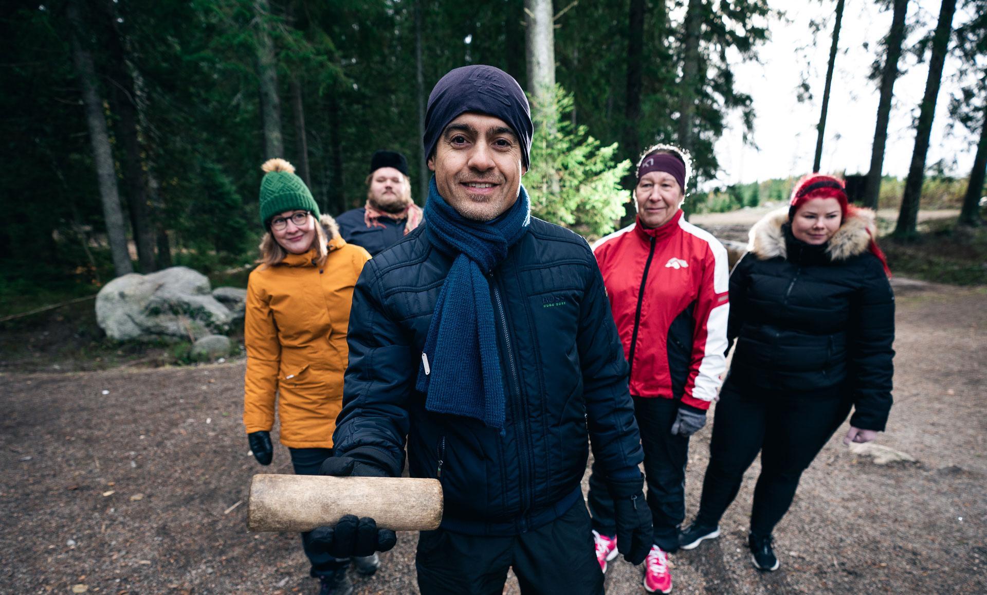 Kuvassa mies etualalla pitelee käsissään Mölkky-palikkaa ja taustalla on neljä muuta henkilöä.