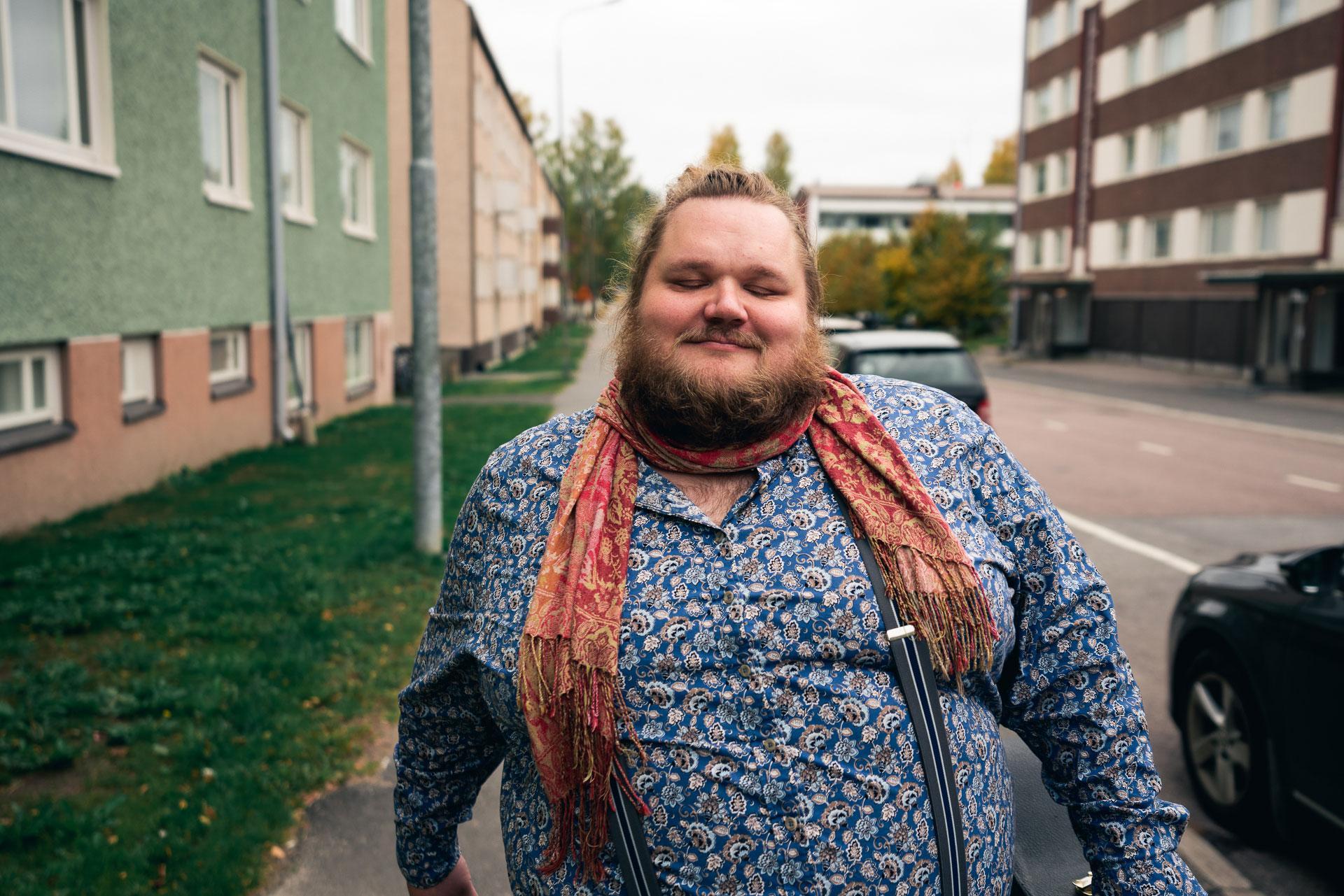 Mies kävelee kaupungin kadulla. Kuvassa miehellä on silmät kiinni ja tyytyväinen ilme kasvoillaan.