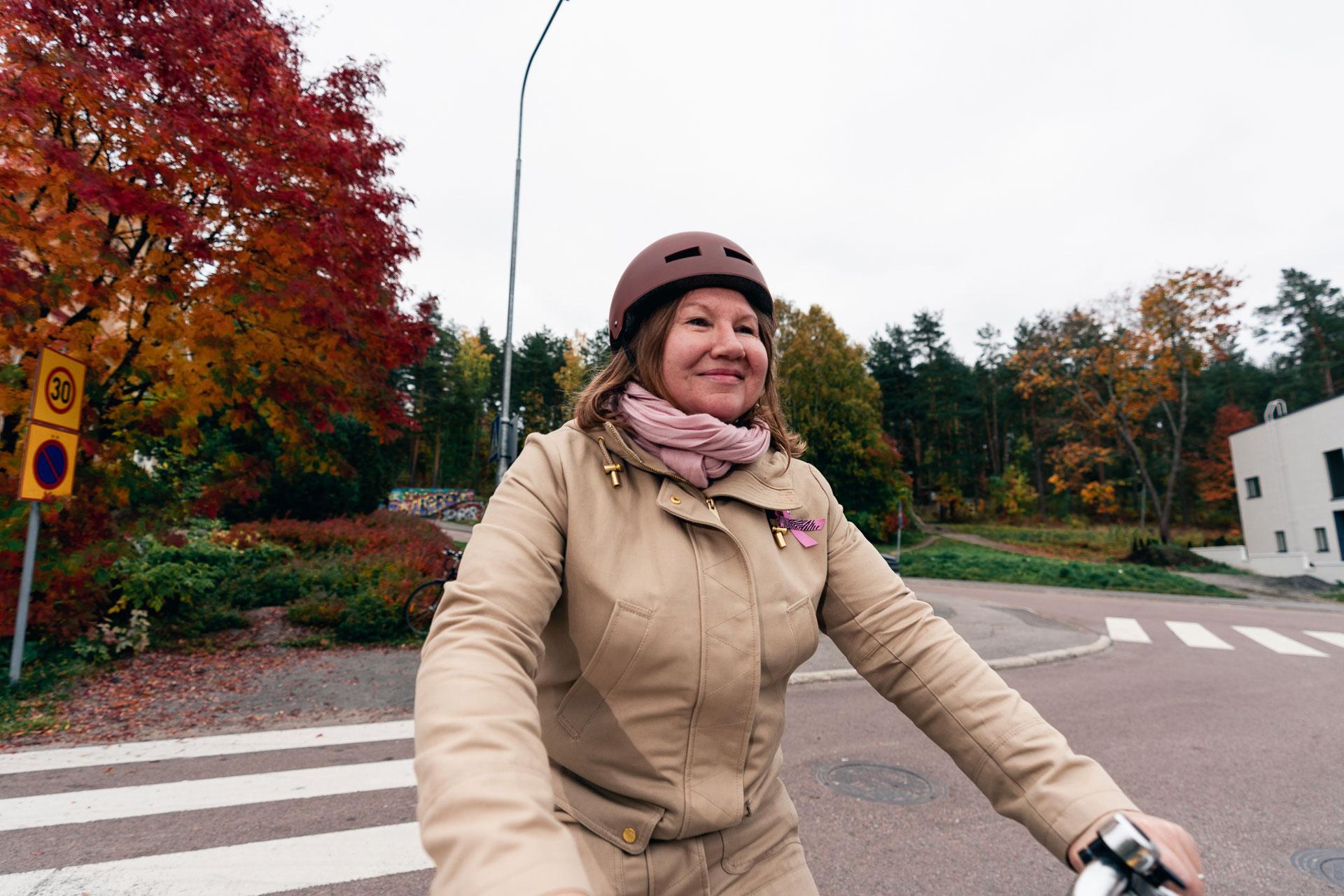 Nainen pyöräilee kypärä päässä kaupunkiympäristössä. Taustalla on syksyisiä puita.