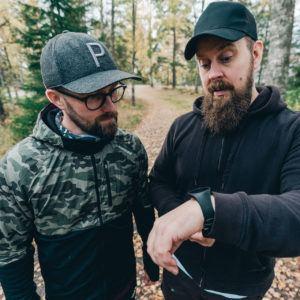Kaksi miestä seisoo metsätiellä ja katsoo toisen miehen ranteessa olevaa aktiivisuusmittaria.